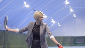Молодая коммерсантка с ботинками в руки теннисе игры профессионально видеоматериал