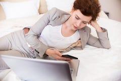 Молодая коммерсантка с компьтер-книжкой на кровати Стоковые Изображения