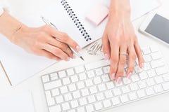 Молодая коммерсантка с красивым маникюром печатая на клавиатуре на рабочем месте стоковые изображения rf