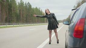Молодая коричнев-с волосами женщина останавливает для езды около сломленной машины сток-видео