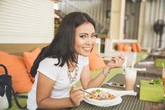 Молодая красивая азиатская женщина в ресторане, наслаждаясь ее едой стоковые изображения rf