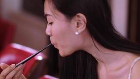 Молодая красивая азиатская женщина ест суши в ресторане видеоматериал