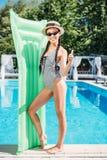 Молодая красивая азиатская женщина представляя с раздувным тюфяком на poolside стоковые изображения