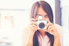 Молодая красивая азиатская женщина принимая фото outdoors с digi DSLR стоковое фото