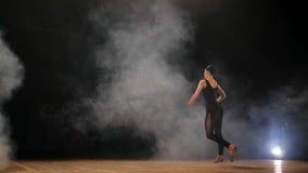 Молодая красивая балерина на балете танцев этапа дыма современном в темноте Женщина в черном костюме выполняет на сцене сток-видео