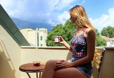 Молодая красивая белокурая девушка сидя на балконе рано утром и выпивая кофе и есть красное зрелое Стоковая Фотография