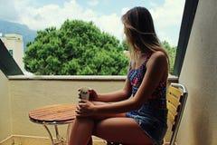Молодая красивая белокурая девушка сидя на балконе рано утром и выпивая кофе и есть красное зрелое Стоковые Изображения