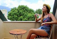 Молодая красивая белокурая девушка сидя на балконе рано утром и выпивая кофе и есть красное зрелое Стоковые Фото