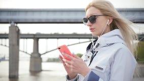 Молодая красивая белокурая женщина слушает музыку на ее смартфоне используя наушники Молодая женщина наслаждается прогулкой впере видеоматериал