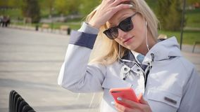 Молодая красивая белокурая женщина слушает музыку на ее смартфоне используя наушники Молодая женщина наслаждается прогулкой впере сток-видео