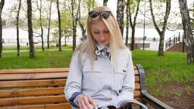 Молодая красивая белокурая женщина читает журнал и отдыхает на скамейке в парке Студент учит английский во время a акции видеоматериалы