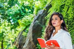 Молодая красивая восточная индийская американская женщина с длинной Красной книгой чтения волос на открытом воздухе на центрально стоковое фото rf