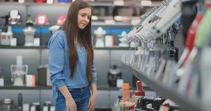 Молодая красивая девушка в голубой рубашке выбирает blender в магазине приборов акции видеоматериалы