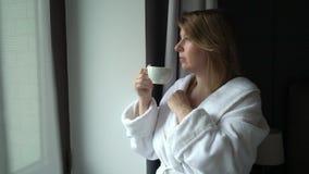 Молодая красивая девушка в кофе купального халата выпивая на утре акции видеоматериалы