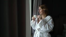 Молодая красивая девушка в кофе купального халата выпивая на утре сток-видео