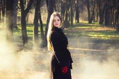 Молодая красивая девушка в перчатках черного пальто красных исследуя дым леса весны паркует стоковые изображения rf