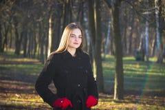 Молодая красивая девушка в перчатках черного пальто красных исследуя весну Forest Park стоковое фото