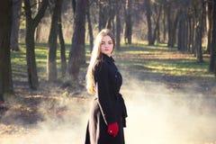 Молодая красивая девушка в перчатках черного пальто красных исследуя дым леса весны паркует стоковые изображения