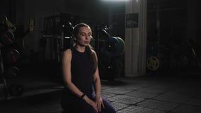 Молодая красивая девушка в спорт формирует отдыхать после тренировки в вечере в спортзале Сидеть на поле и активно делать brea видеоматериал