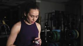 Молодая красивая девушка в спорт формирует отдыхать после тренировки в вечере в спортзале Он принимает бутылку воды и гасит его сток-видео