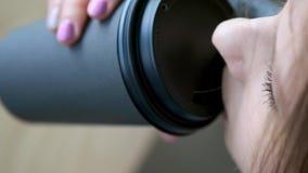 Молодая красивая девушка в стильном кафе выпивает кофе в утре перед работой Сидит напротив окна Он выпивает видеоматериал
