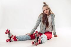 Молодая красивая девушка в sporty стильных одеждах с длинными волосами на четырехколесных роликах изолированных на предпосылке стоковые фотографии rf