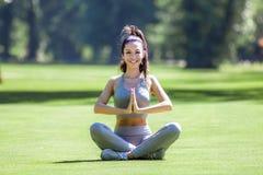 Молодая красивая девушка делая йогу работает внешнее стоковые фото