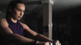 Молодая красивая девушка делая тренировки в спортзале Поднимает руки с гантелями металла вперед Фокус камеры на гантелях видеоматериал