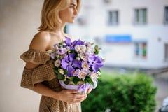 Молодая красивая девушка держа корзину фиолетовых цветков Стоковые Фото