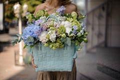 Молодая красивая девушка держа огромную корзину нежных цветков Стоковые Фото