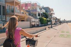 Молодая красивая девушка ехать велосипед вниз с пляжа Венеции Стоковое Фото