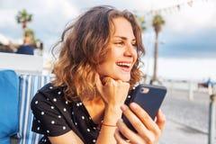 Молодая красивая девушка женщины сидя в кафе улицы усмехаясь с Стоковые Фотографии RF