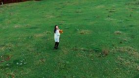 Молодая красивая девушка имея потеху в лесе осени она держит пук желтых листьев Она бежит и смотрит акции видеоматериалы