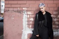 Молодая красивая девушка моды снимая outdoors около кирпичной стены дома стоковая фотография
