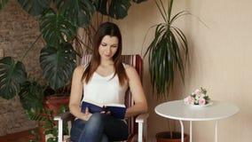 Молодая красивая девушка принимает книгу от таблицы и начинает прочитать Женщина читая книгу сидя в стуле видеоматериал