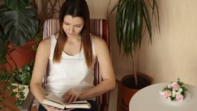 Молодая красивая девушка принимает книгу от таблицы и начинает прочитать Женщина читая книгу сидя в стуле сток-видео