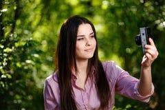 Молодая красивая девушка принимая selfie с ретро камерой фильма Стоковые Фото