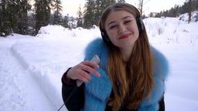 Молодая красивая девушка самостоятельно в лесе зимы она слушает музыку через наушники и танцы Она ` s счастливое медленно сток-видео