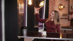 Молодая красивая девушка сидит в кафе и выпивает очень вкусный кофе и делает selfie акции видеоматериалы