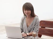 Молодая красивая девушка сидя в кофейне с компьтер-книжкой и усмехаться стоковые изображения