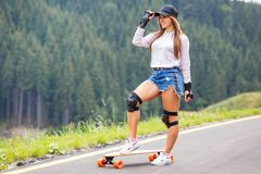 Молодая красивая девушка стоя с доской на дороге стоковые изображения