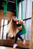 Молодая красивая девушка с длинными светлыми волосами одетыми в одеждах спорта делает фитнес на зеленом воздушном шелке в стоковое изображение