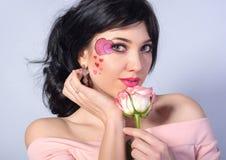Молодая красивая девушка с сердцем на ее щеке с розой Стоковое Изображение