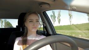 Молодая красивая девушка управляя автомобилем видеоматериал