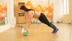 Молодая красивая девушка фитнеса работая в спортзале молодая женщина трясет ее ноги отдыхая на шарике акции видеоматериалы