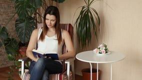 Молодая красивая девушка читая книгу сидя в стуле Женщина смеется над на читать книгу взволнованности положительные видеоматериал