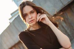 Молодая красивая длинная фотомодель девушки волос ветра на улице города стоковое изображение