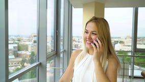 Молодая красивая женатая женщина идет вдоль большого окна и бесед по телефону акции видеоматериалы