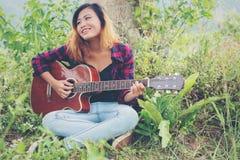 Молодая красивая женщина битника играя гитару сидя на траве внутри Стоковое Изображение RF