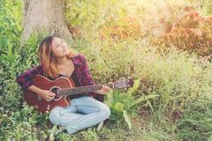 Молодая красивая женщина битника играя гитару сидя на траве внутри Стоковые Изображения RF